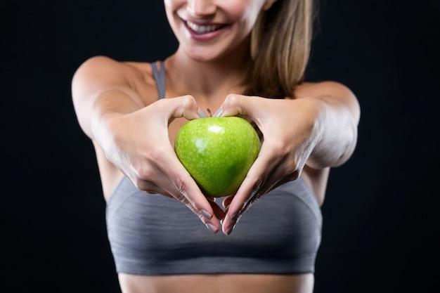 黒い背景の上にりんごを持っている美しい若い女性。 無料写真