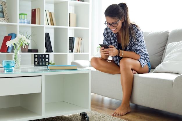 彼女の携帯電話を自宅で使っている美しい若い女性。 無料写真