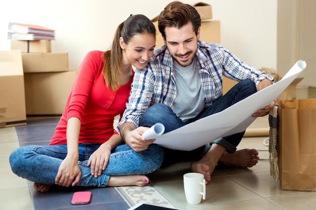 彼らの新しい家の青写真を見ている若いカップル 無料写真