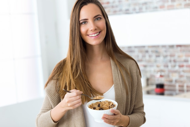 美しい若い女性が家庭で穀物を食べる。 無料写真