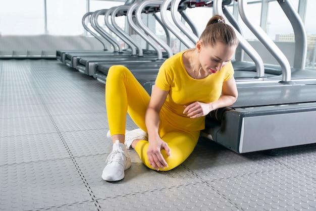 座っていると痛みを感じて負傷した膝を持つ若い女性 Premium写真