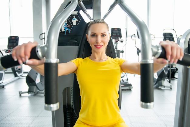 ジム内の運動マシンでワークアウト陽気な若い大人の白人女性の胴体の肖像画 Premium写真