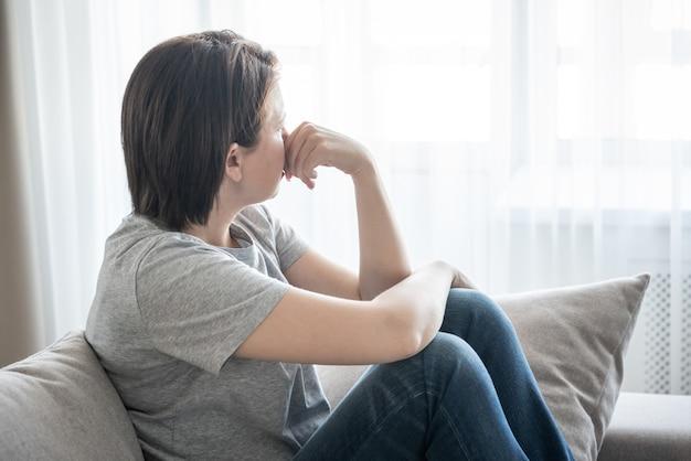 悲しい少女が自宅でソファに座っている問題の概念 Premium写真