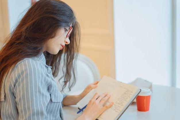 スタイリッシュなカフェでレクリエーションの時間を楽しんでメモ帳でメモを作る魅力的な若い女性 Premium写真