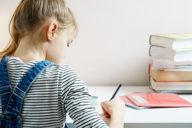 Подросток, изучая и делая ее домашнюю работу, держа ручку с копией пространства Premium Фотографии
