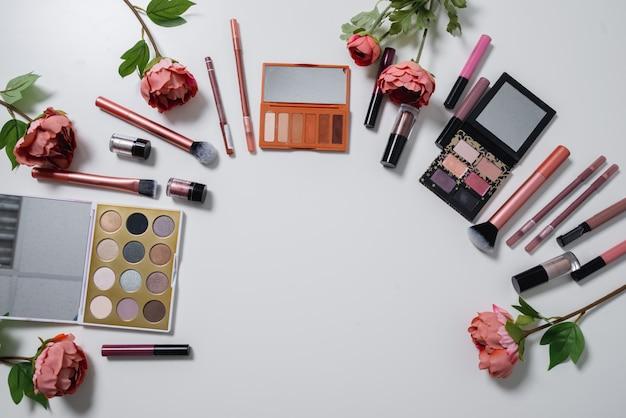 Декоративная плоская композиция с косметикой и цветами. плоская планировка, вид сверху на белом фоне Premium Фотографии
