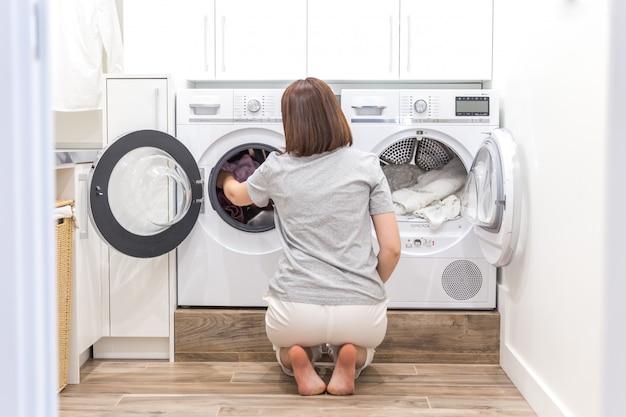 Женщина кладет одежду в стиральную машину для стирки Premium Фотографии