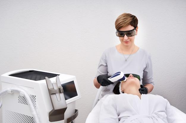 Молодая женщина, получающая лазерное лечение в косметологической клинике Premium Фотографии