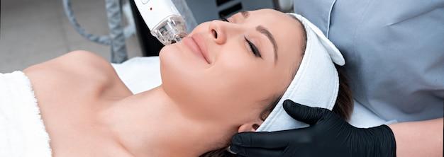 美容クリニックでレーザー治療を受ける若い女性 Premium写真