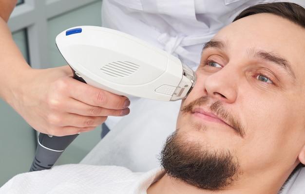 美容クリニックでレーザー治療を持っている人 Premium写真