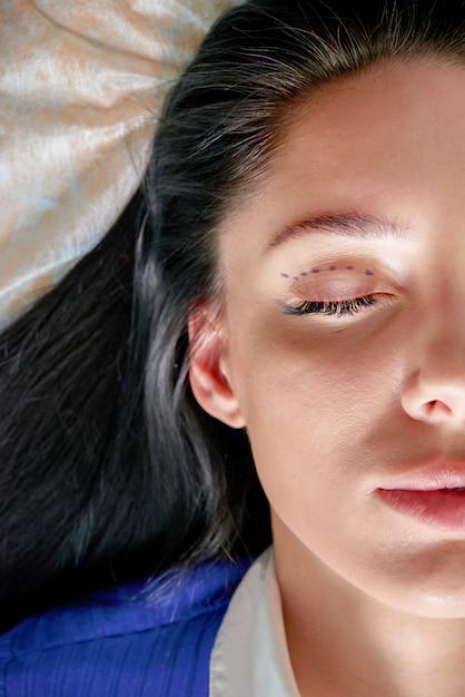 整形外科医と美容整形の前に修正線を持つ若い女性、目に線を引く Premium写真