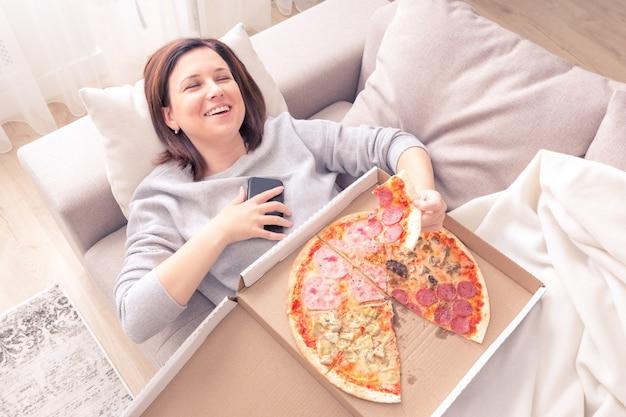 ソファの上に敷設、ピザを食べて、携帯電話のオレンジ色のトーンを保持している笑っている若い女性の肖像画 Premium写真