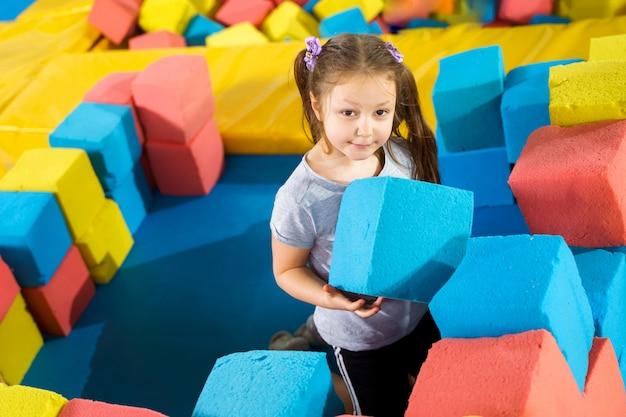 Дети играют с мягкими кубиками в сухом бассейне в игровом центре. детская площадка с пеноблоками в батутном клубе Premium Фотографии