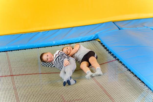 Счастливые улыбающиеся маленькие дети, лежа на батуте в развлекательном центре Premium Фотографии