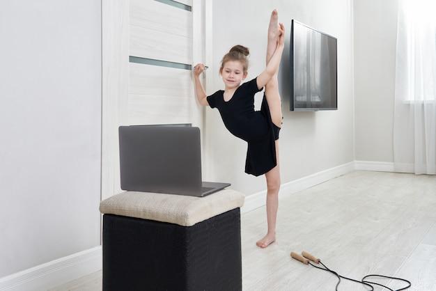 Маленькая девочка делает гимнастику дома с помощью онлайн-обучения с портативным компьютером Premium Фотографии