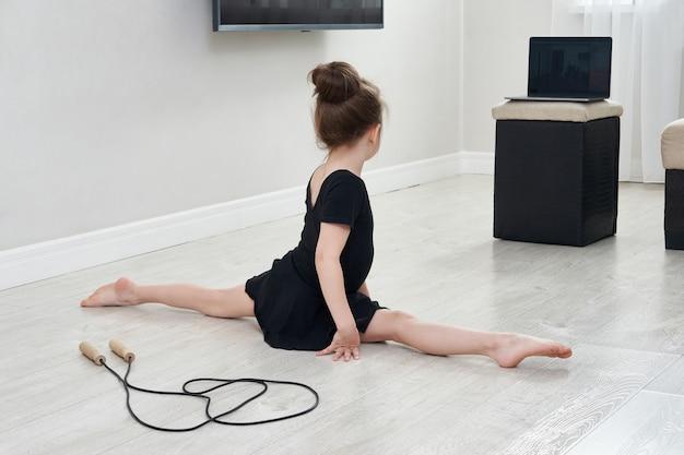 Маленькая девочка, делающая гимнастику, тренируется дома, используя онлайн-обучение с ноутбуком, концепцию интернет-образования Premium Фотографии