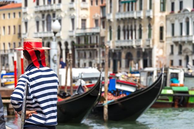 Гондольер стоит рядом с гондолой в ожидании клиента Premium Фотографии