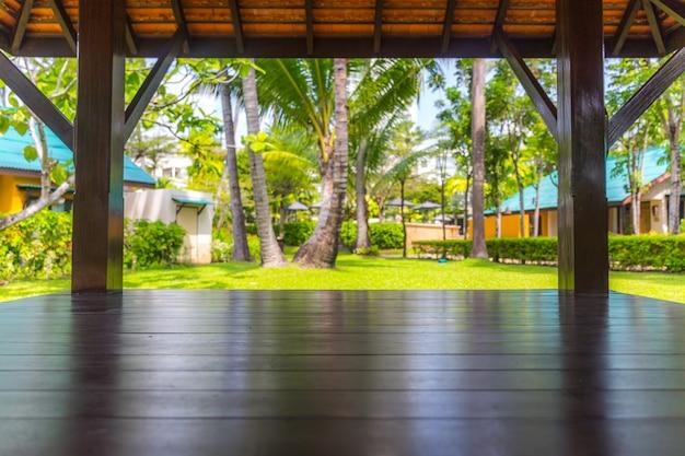 ヤシの木の背景を持つ木製テーブルの上部 Premium写真
