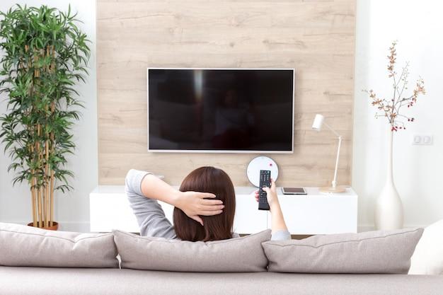 部屋でテレビを見ている若い女性 Premium写真