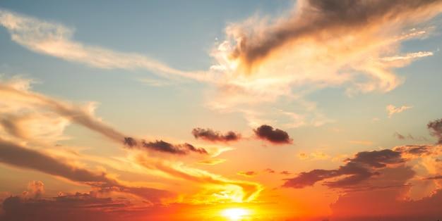 ドラマチックなオレンジと赤の夕焼けや日の出の空の雲 Premium写真