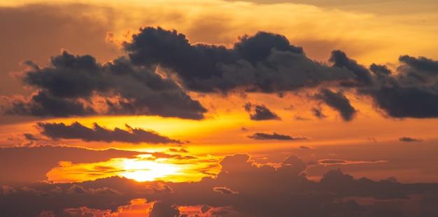 雲と劇的なオレンジと赤の夕焼けや日の出の空 Premium写真