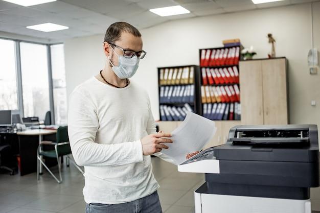 Парень в защитной маске копирует документы Premium Фотографии
