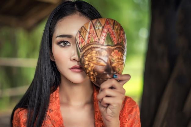伝統的な衣装を着た美しいバリの女性、バリ島とインドネシアのマスク文化 Premium写真