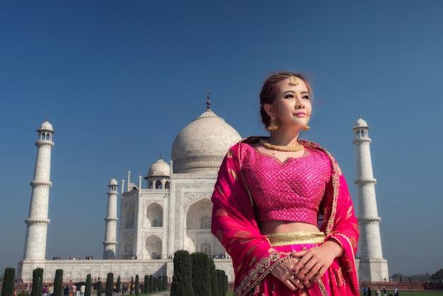 伝統的なドレス衣装、インドの典型的なサリー/サリードレスアイデンティティ文化を身に着けているアジアの女性の美しい女性。タージ・マハル・シーニックインドのアグラにあるタージ・マハルの記念碑の朝の景色。 Premium写真