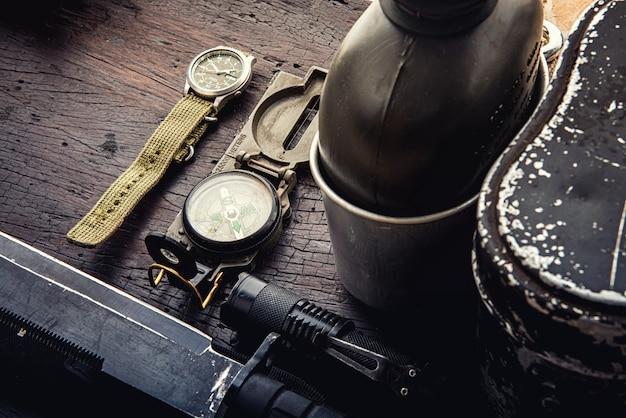 出発のための軍事戦術機器。木製の背景にサバイバルハイキングギアの品揃え Premium写真