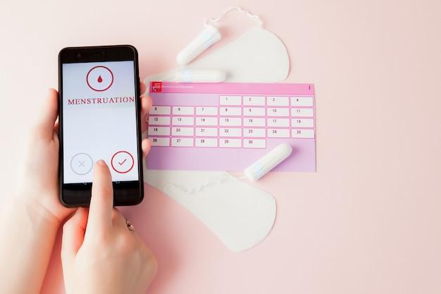 Тампоны, женские, гигиенические прокладки на критические дни, женский календарь, болеутоляющие таблетки при менструации на розовом фоне. отслеживание менструального цикла и овуляции Premium Фотографии