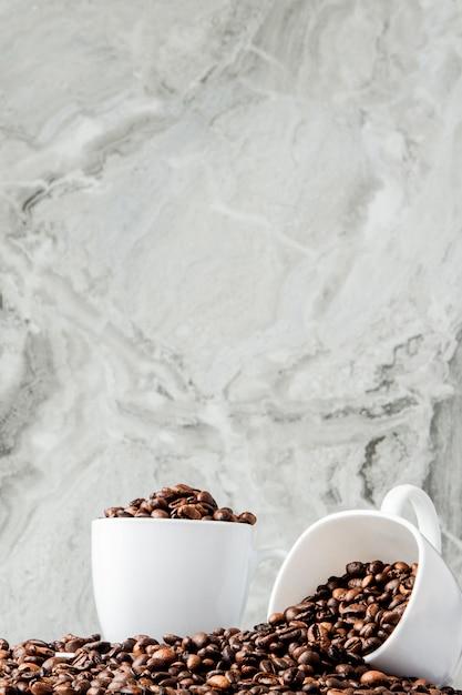 カップと大理石の背景にコーヒー豆のブラックコーヒー。 Premium写真
