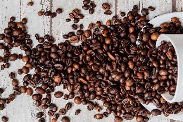 白いカップと明るい木製の背景にコーヒー豆のブラックコーヒー。 Premium写真