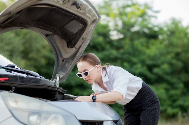 彼女の車が壊れた後、道端で若い女性彼女はフードを開けて損傷を確認しました Premium写真