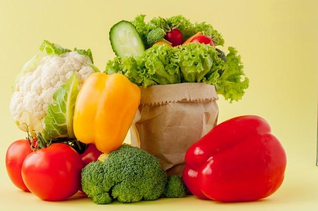 Органические овощи брокколи огурцы болгарский перец яблоки в оберточной бумаге крафт продуктовый мешок. здоровое питание, диетическое волокно веганский Premium Фотографии
