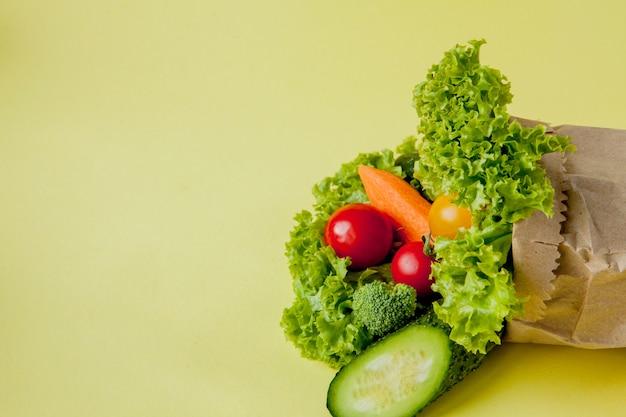 Органические овощи брокколи огурцы болгарский перец яблоки в оберточной бумаге крафт-пакет Premium Фотографии