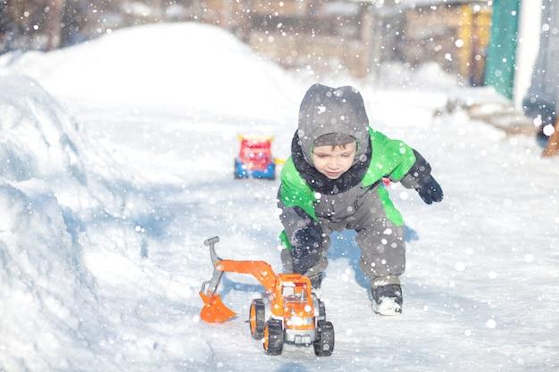 Портрет милого маленького малыша сидя на снеге и играя с его желтой игрушкой трактора в парке. ребенок, играющий на открытом воздухе. счастливый мальчик с игрушкой конструкции. концепция образа жизни Premium Фотографии