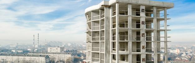 都市で建設中の背の高いマンションのコンクリートフレームの空撮のパノラマ Premium写真