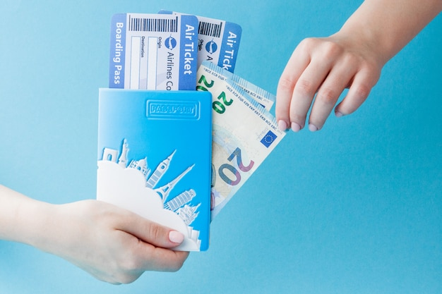Паспорт, евро и авиабилет в руке женщина на синем. путешествия, копия Premium Фотографии