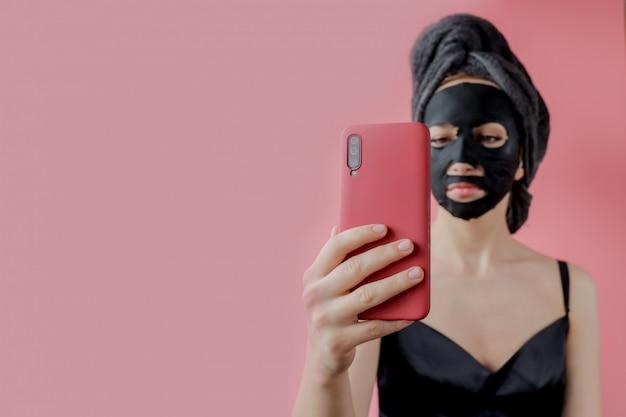 Молодая женщина применять черные косметические ткани маска для лица и телефон в руках на розовой стене. маска-пилинг для лица с древесным углем, спа-салон красоты, уход за кожей, косметология. закрыть Premium Фотографии