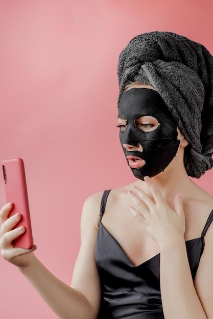 Молодая женщина применять черные косметические ткани маска для лица и телефон в руках на розовом фоне. маска-пилинг для лица с древесным углем, спа-салон красоты, уход за кожей, косметология. закрыть Premium Фотографии