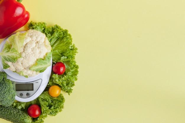 黄色の背景の上に花瓶で新鮮な野菜。健康的な食事、ダイエット計画、減量、デトックス、有機農業の概念 Premium写真