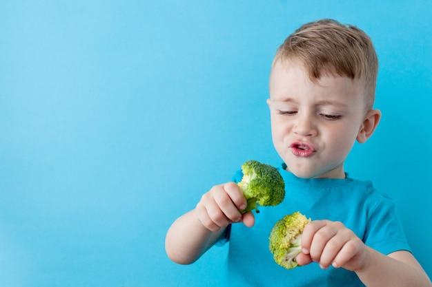 青の背景に彼の手でブロッコリーを保持している小さな子供。ビーガンと健康の概念 Premium写真