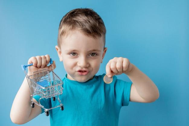 Мальчик в синей футболке держит корзину и монета на синем фоне. концепция покупки и продажи. Premium Фотографии