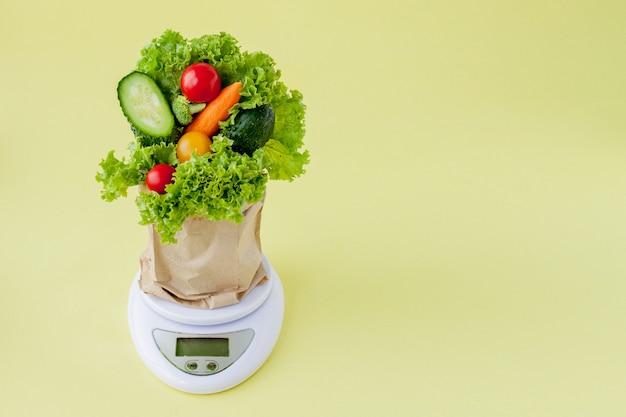 黄色の背景のスケールで新鮮な野菜。ビーガンと健康の概念。 Premium写真
