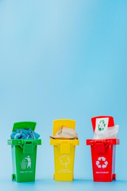青の背景にリサイクルマークの付いた黄色、緑、赤のごみ箱。街を整頓し、リサイクルのシンボルを残します。自然保護のコンセプト Premium写真