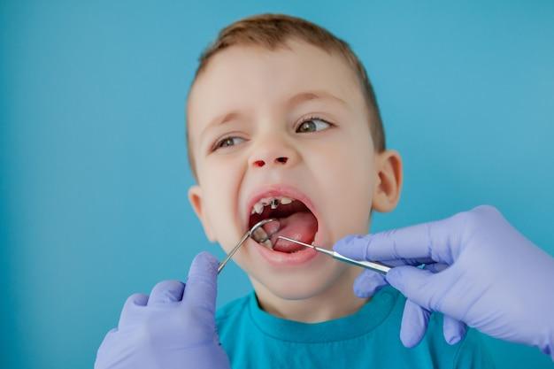 Крупным планом руки стоматолога с помощником в синих перчатках лечат зубы ребенку, лицо пациента закрыто Premium Фотографии