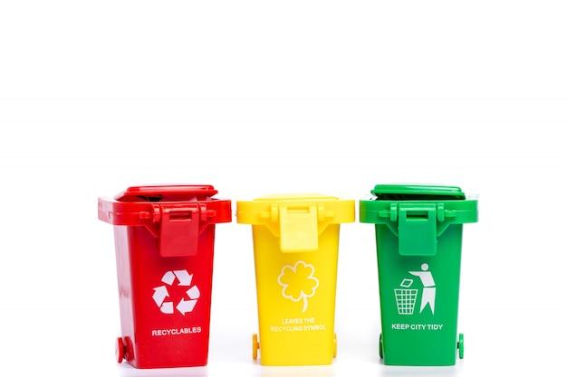 白い背景に分離されたリサイクルマークの付いた黄色、緑、赤のごみ箱 Premium写真