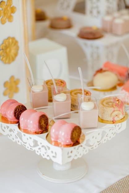 Десерты с фруктами, мусс, печенье. различные сладкие пирожные, маленькие красочные сладкие пирожные, макароны и другие десерты в виде сладкого буфета. моноблок на день рождения. Premium Фотографии