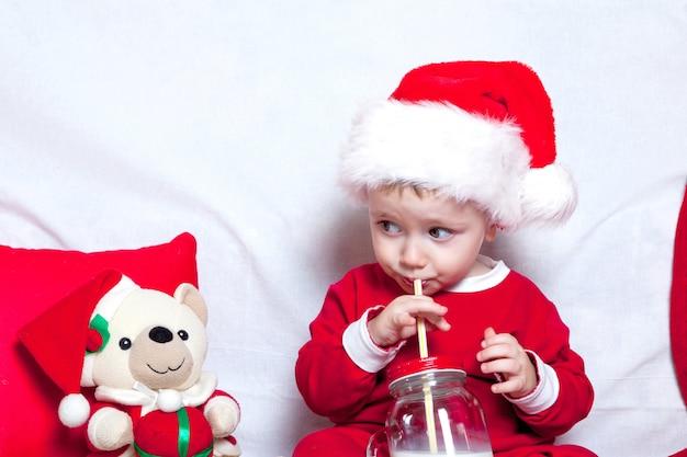 赤い帽子の小さな子供はクッキーとミルクを食べます。赤い帽子の赤ちゃんをクリスマス。年末年始とクリスマス Premium写真