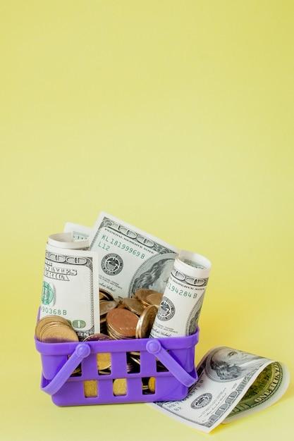 コインと黄色の背景にドル札付きショッピングバスケット Premium写真